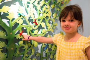 A visitor adds their ribbon to the Wishing Tree in Painting With Rainbows - Michael Foreman Exhibition.